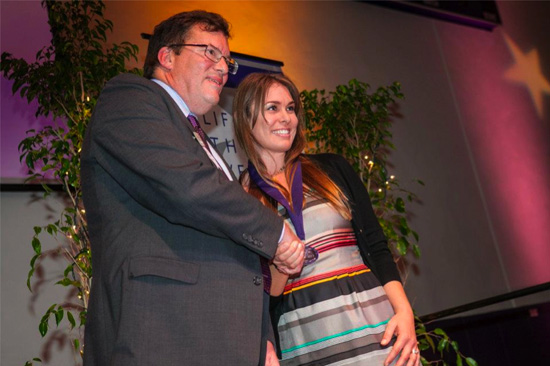 Amber Sims Hinterplattner accepting award from CLU President Chris Kimball